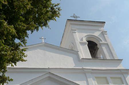 sainthood: Faith Catholic Church against the blue sky and tree.