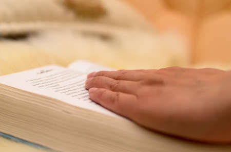 bookish: Hands turn a book and lead it to pages.
