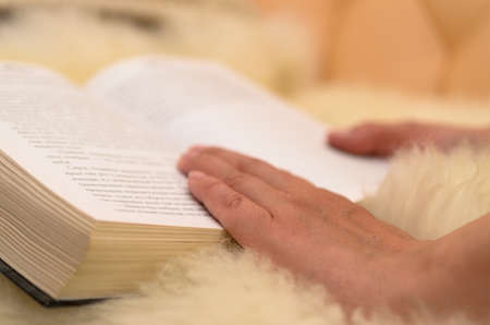 Hands turn a book and lead it to pages.
