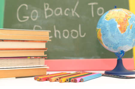 School supplies on a background of a school board with an inscription and on a light background Stock Photo