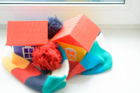 Toy house on the window sill wrapped in a scarf. Warming up the house.