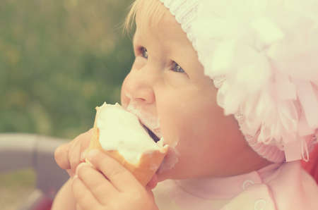 A little girl is eating ice cream and smeared her face Stock Photo