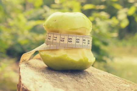 A green apple with a green ribbon and a measuring tape