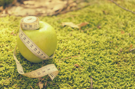 Green apple on green grass with measuring tape and without