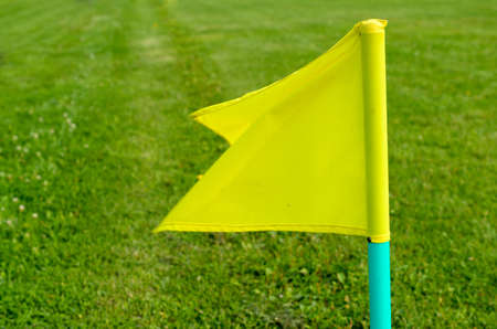Yellow flags on the green grass of a football playing field Stock Photo
