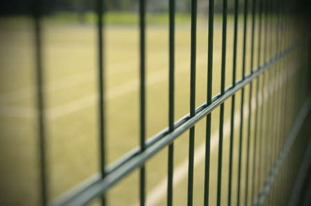barbed wire fence: Metal fencing of the tennis court with the effect of vignetting