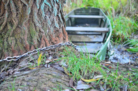 The old boat is tied to a tree trunk by a chain Stock Photo
