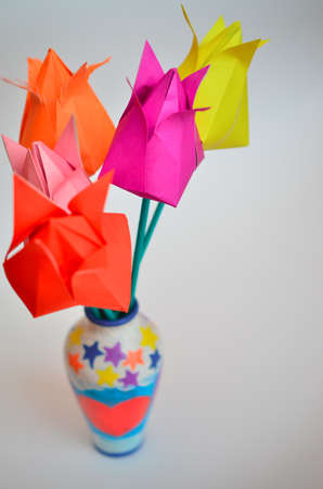 Multicolored tulips handmade from paper by March 8 on a light background