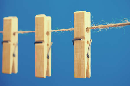 A few clothespins on a rope on a blue background Stock Photo