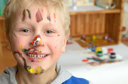 The childs face, soiled with paint, laughs funny and cheerfully