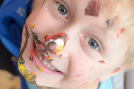 The childs face, soiled with paint, laughs funny and cheerfully.