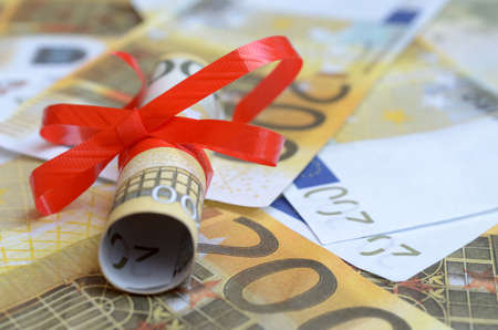 Rolls of money in a gift ribbon on bills of dollars and euros Stock Photo