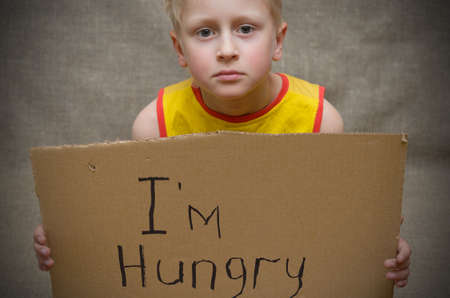 A hungry boy in a yellow T-shirt with a cardboard tablet with the inscription I'm hungry . The social problem 스톡 콘텐츠