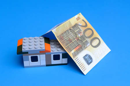 Toy house and money bills. The concept of loans for housing