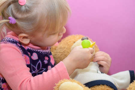 The little girl is playing with any soft toys