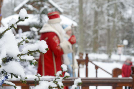 Santa Claus and Snow Maiden go out onto the terrace of their manor in the winter against the background of snow-covered fir trees
