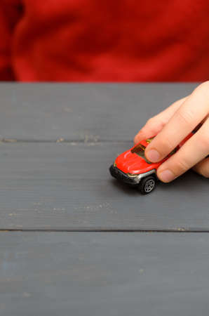The hand of the child plays with a red typewriter on a wooden surface of a dark color Reklamní fotografie