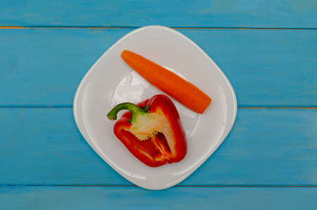 Bulgarian red pepper with carrots on a white plate. Wooden blue background. The concept of healthy eating Reklamní fotografie