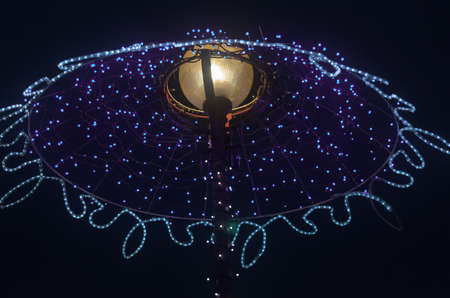 Night street lamp with a garland of blue LEDs