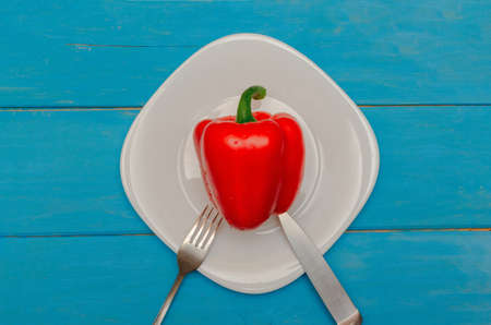 Bulgarian red pepper on a white plate. Wooden blue background. The concept of healthy eating