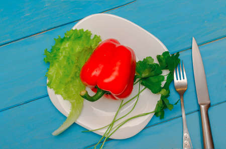 Bulgarian red pepper with lettuce on a white plate. Wooden blue background. The concept of healthy eating