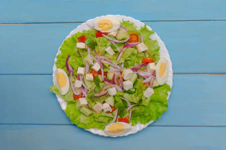 Salad of vegetables and lettuce and feta on a white plate. Blue wooden background. The concept of healthy eating
