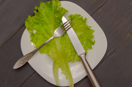 Salad leaves on a white plate with fork and knife. Gray wooden background. The concept of healthy eating