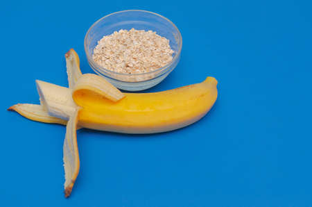Ripe banana and glass of oatmeal on a blue background. The concept of healthy eating Stock fotó