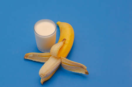 Ripe banana and a glass of yogurt on a blue background. The concept of healthy eating