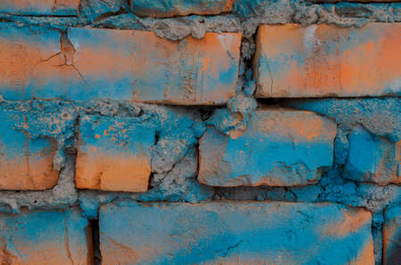 A stretch of brick wall painted with blue paint.