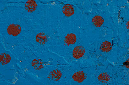 The section of the wall, painted with blue paint with burgundy patches.