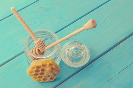 Honey and honey accessories for its use on a blue wooden background 免版税图像