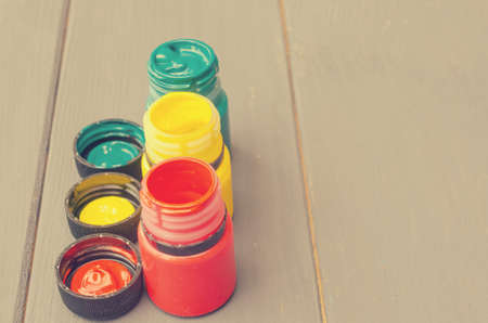 Jars with green yellow and red paints on a gray wooden background. Stock fotó