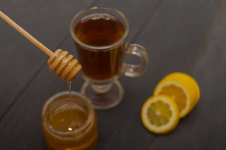 Composition of a cup of tea, sliced lemon and a jar of honey. Stock fotó