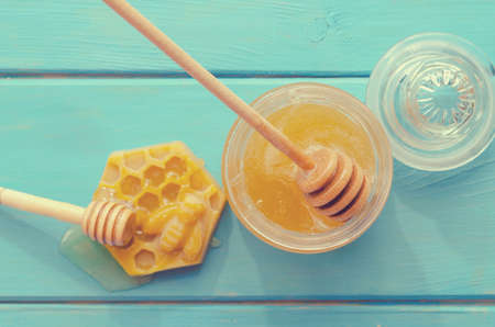 Honey and honey accessories for its use on a blue wooden background Stock fotó