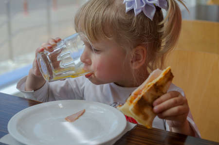 Little girl with an appetite for eating pizza in a cafe.