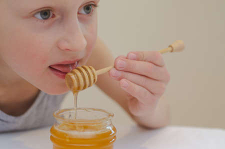 The boy using a spoon for honey eats it from the jar.