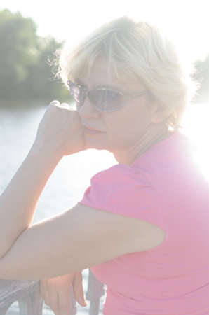 A woman of 45-50 years old sits with sadness near the river on the embankment street.