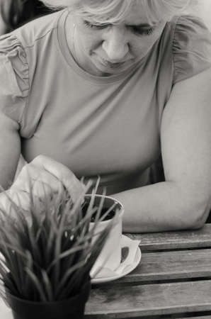 A woman of 45-50 years old sits sadly in a cafe with a cup of tea.