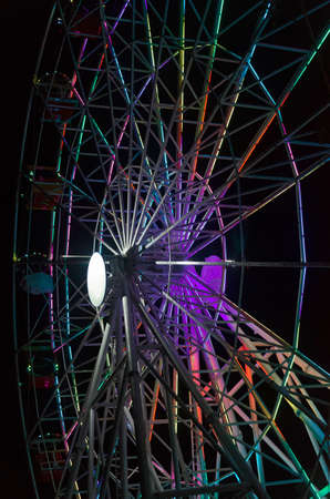 Attraction in the form of a Ferris wheel in the dark with beautiful lighting.