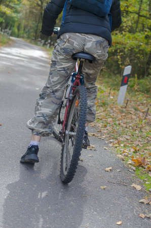 A girl in camouflage pants on a bicycle stands on the road.