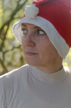 A woman in a hat of Santaclaus with a sly evil face among the autumn foliage as a harbinger of the coming winter.