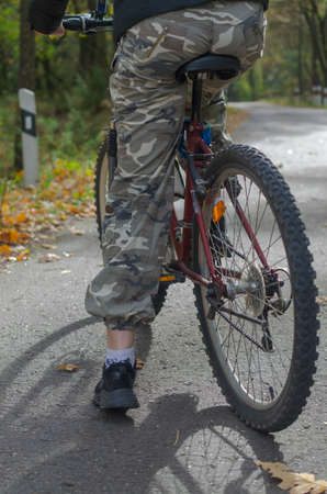 A girl in camouflage pants on a bicycle stands on the road