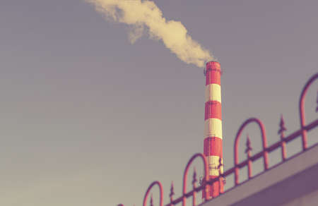 The factory chimney emits a blue poisonous smoke Stock Photo