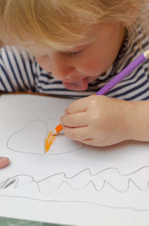 A little blonde girl draws with a pencil on paper.