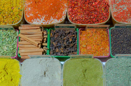 Eastern culinary seasonings of different colors on the counter Stock Photo