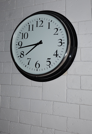 Black clock on the grey brick wall