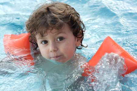 photo of an adorable boy learning to swim Stock Photo