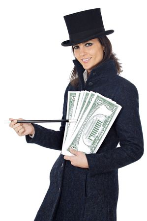 attractive business woman with a magic wand and hat making appear giant dollars (a over white background) photo