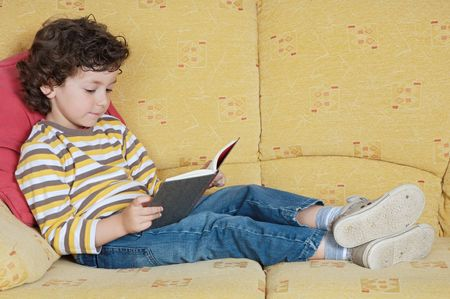 adorable happy boy reading in the armchair of your house photo
